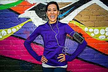 Hispanic runner smiling near graffiti wall