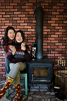 Chinese mother and daughter hugging near fireplace
