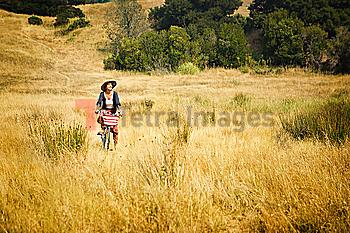 Caucasian woman riding bicycle in field