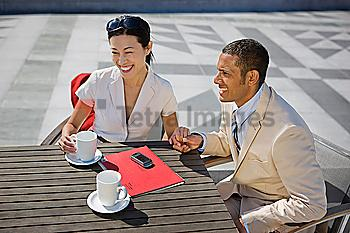 Couple holding hands and drinking coffee outdoors