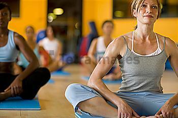 Women practicing yoga in health club