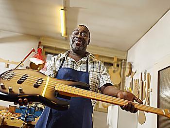 Black craftsman holding electric guitar in workshop