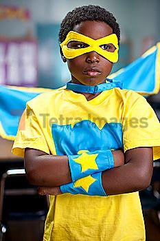 African American boy wearing superhero costume in classroom
