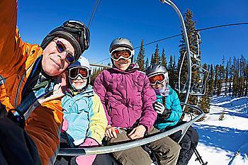 Family riding ski lift together