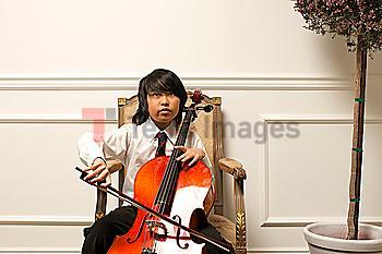 Vietnamese boy playing cello on elegant chair