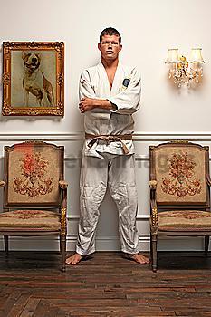 Serious Caucasian man in martial arts uniform standing in elegant room