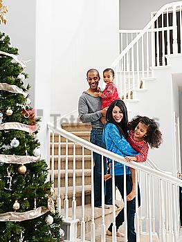 Family descending stairs on Christmas morning