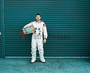 Astronaut carrying television on city street