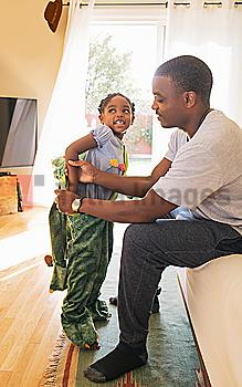African American father helping daughter put on costume