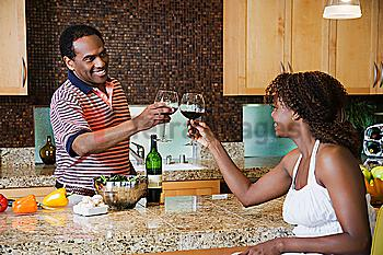 African couple toasting with red wine in kitchen