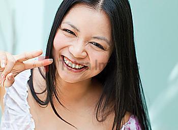 Smiling Vietnamese woman making peace sign gesture