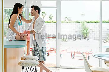Husband smiling at wife sitting on counter