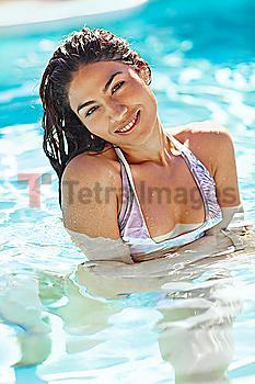 Hispanic woman swimming in swimming pool
