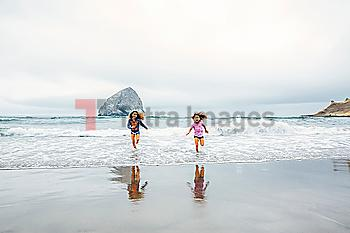 Mixed race sisters running on beach