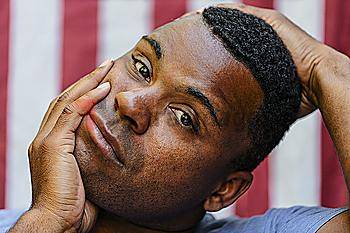 Close up of concerned Black man  in front of American flag