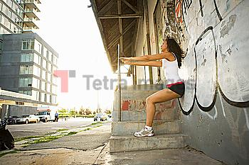 Hispanic woman exercising against graffiti covered wall