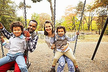 Family sitting on swings in park