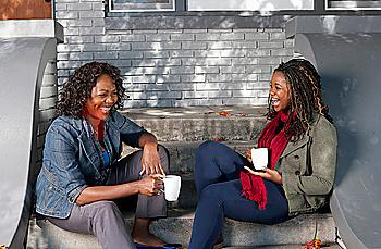 Black mother and daughter sitting on front stoop drinking coffee