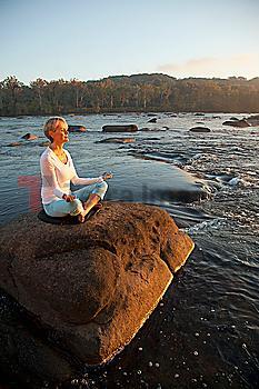 Woman practicing yoga on rock near ocean