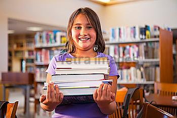 Mixed race girl carrying library books