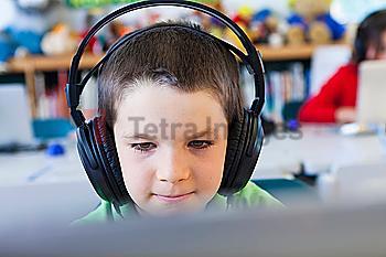 Caucasian student in headphones using laptop in classroom