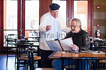 Caucasian man talking to chef in restaurant
