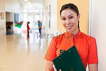 Mixed race teacher holding clipboard in school hallway