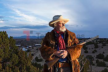 Caucasian man holding gun in dusty landscape