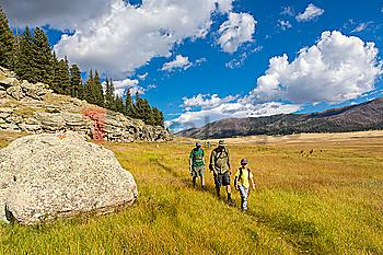 Caucasian men and boy hiking in grassy remote landscape