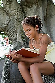 Hispanic girl reading book on tree trunk
