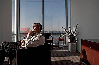 Mixed race businessman sitting in armchair and looking pensive