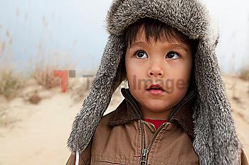 Mixed race boy wearing fur hat