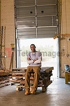 Black man sitting on pallets in warehouse