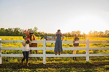 Caucasian family petting horses in rural landscape