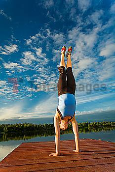 Caucasian woman practicing yoga on dock on still lake, Anchorage, Alaska, United States