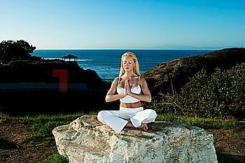 Caucasian woman practicing yoga near ocean