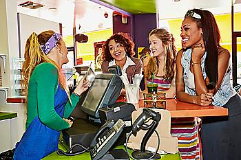 Women ordering from server in cafe