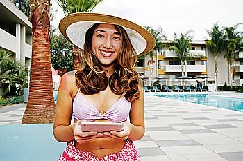Hispanic woman using digital tablet at swimming pool