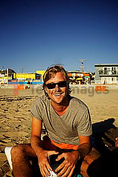 Smiling Caucasian man sitting on beach
