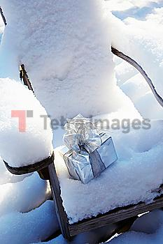 Christmas gift on chair in snow