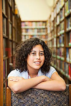Mixed race girl leaning on chair in library