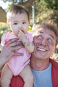 Father playing with baby girl outdoors