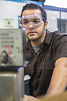 Hispanic worker operating machinery in factory