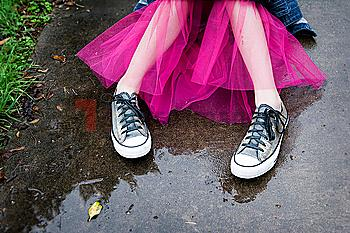 Caucasian girl wearing sneakers and tutu in puddle