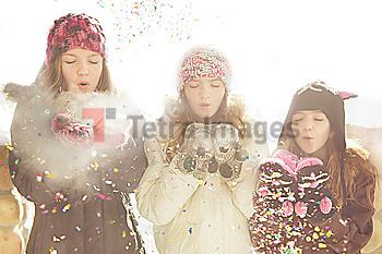 Caucasian girls blowing snow off mittens