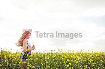 Caucasian teenage girl standing in field of flowers