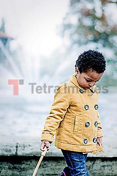 Girl in yellow coat walking in park
