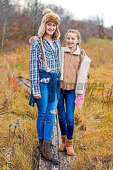 Sisters smiling on wooden walkway in field