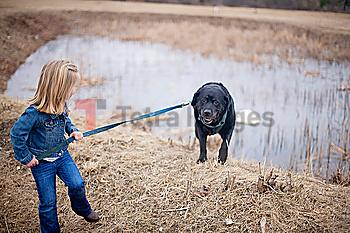 Girl pulling dog on leash near rural pond