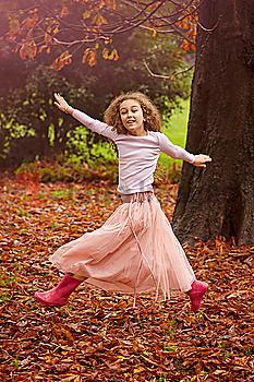 Caucasian girl jumping for joy in autumn leaves